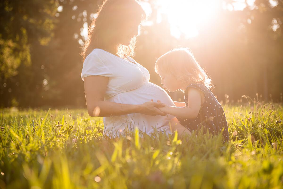 Schwangere Mutte mit Kleinkind auf Sommerwiese